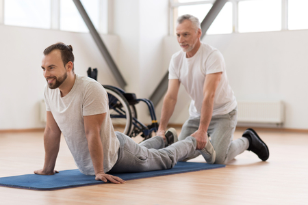 Cheerful physical therapist stretching the handicapped in the gym Stock Photo