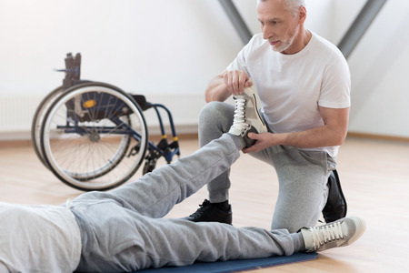 orthopedist: Concentrated aged orthopedist helping the disabled patient in the gym