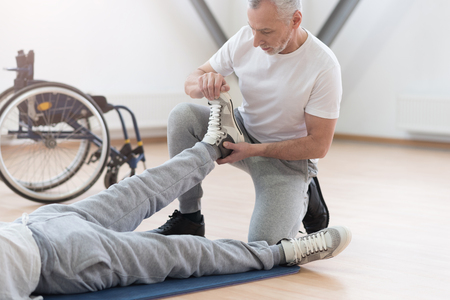 orthopedist: Skillful coach stretching limbs of the disabled in the gym Stock Photo