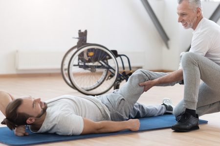 orthopedist: Friendly orthopedist stretching the disabled individual in the gym Stock Photo