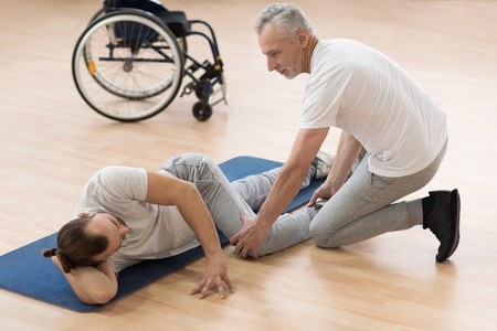 orthopedist: Outgoing physical therapist stretching the disabled patient in the gym