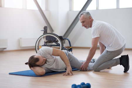 mindful: Mindful physical therapist stretching the disabled man in the gym