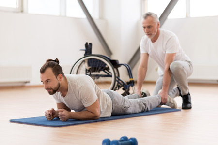 orthopedist: Peaceful physical therapist stretching the disabled patient in the gym