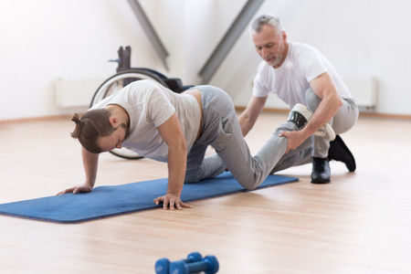 Aged physical therapist stretching the handicapped in the gym Stock Photo