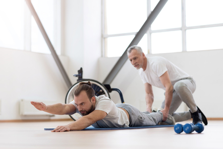Charismatic physical therapist working out with handicapped in the gym Stock Photo