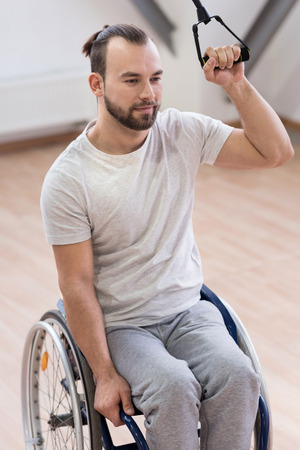 potěšen: Handsome young disabled stretching the cable in the gym