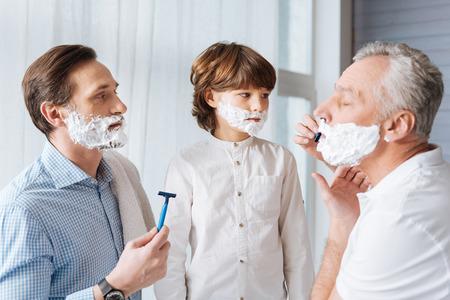 Pleasant aged man holding a razor