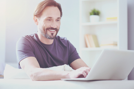 Cheerful adult man workign at home Stock Photo