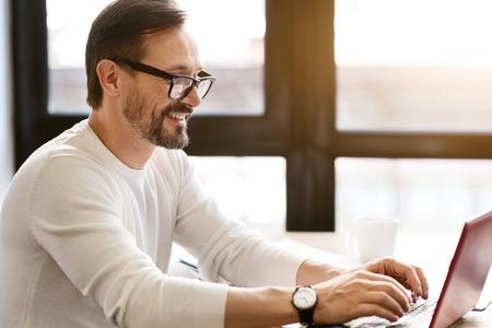 カフェでノート パソコンを使用して魅力的なひげを生やした男