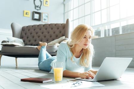 Mujer alegre que usa la computadora portátil en la sala de estar