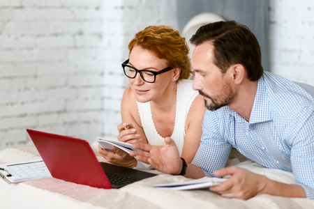 Focused positive couple using laptop at home Stock Photo