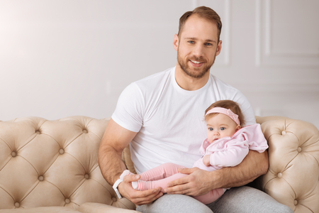 Delighted bearded man resting with his daughter