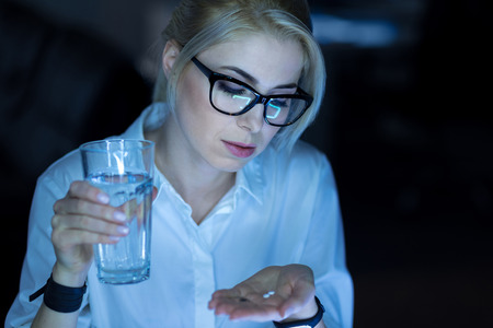 Concentrated woman taking tablets in the office Banco de Imagens