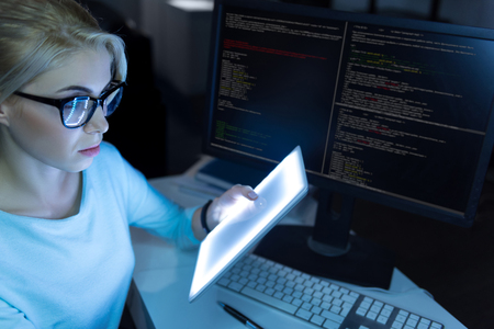 Smart IT girl working in the dark lighted room
