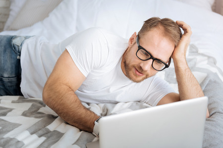 informational: Relaxed young freelancer using laptop and working at home