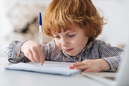 diligente: Focused diligent child writing an essay