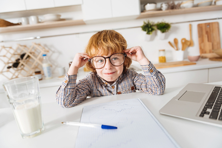 Charming ginger kid sitting in a sunlit kitchen