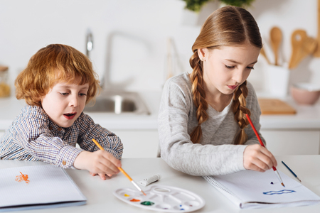 Determined creative siblings painting in the kitchen Stock Photo