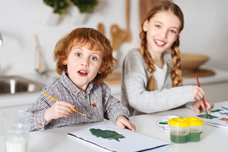 Excited talented siblings drawing some greens Stock Photo