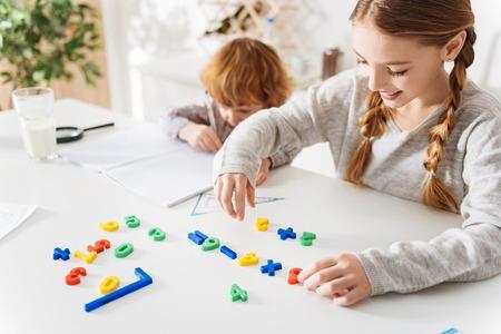 Enthusiastic helping sister arranging formulas Stock Photo