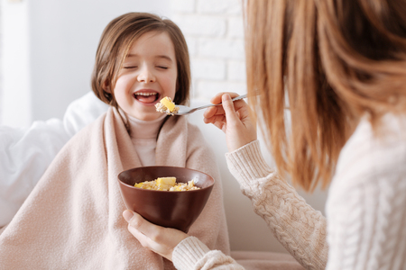 concern: Positive little girl having breakfast with her mother Stock Photo