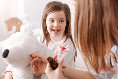 concern: Professional doctor giving pills to little girls toy Stock Photo