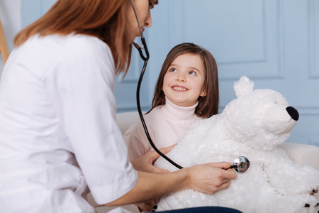 Positive little girl visiting a doctor with her fluffy toy