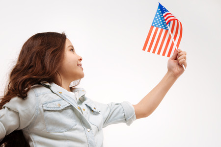 Active little girl showing flag of America in the studio