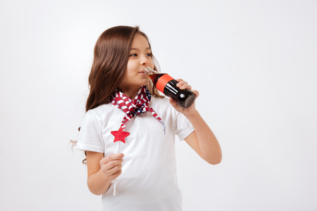 Delighted little girl drinking in the studio Stock Photo
