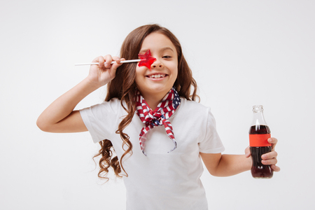 Playful little girl holding bottle and lollipop in the studio