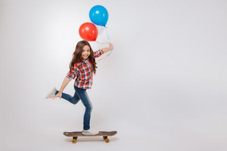 Outgoing girl using skateboard in the studio