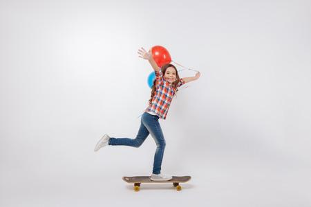 Talented little child skateboarding in the studio