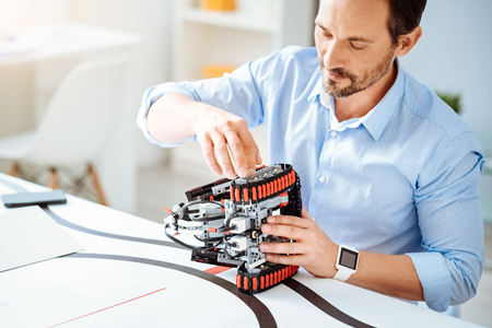 Professional adult engineer working on the robot Stock Photo