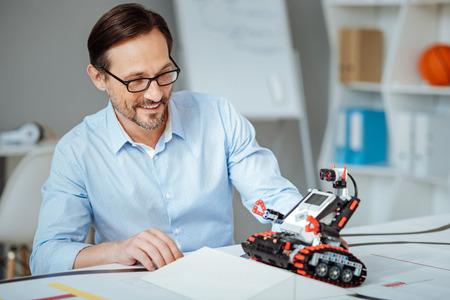Joyful adult engineer testing the robot Stock Photo
