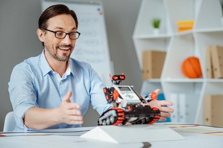 Cheerful engineer testing the robot
