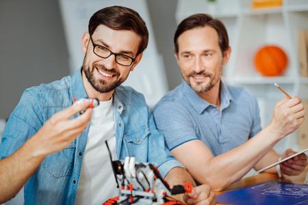 Positive engineers testing robot Stock Photo
