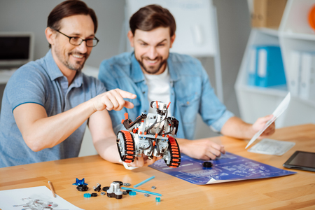 Positive engineers examining the robot