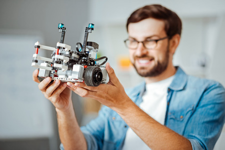 Positive professional engineer holding robot