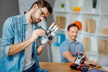Pleasant concentrated engineeer examining robot