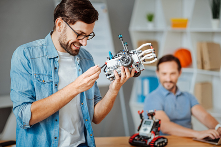 Cheerful engineer constructing the robot