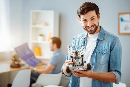Overjoyed engineer testing robot