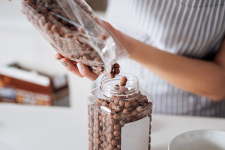 Neat girl putting chocolate chips into a jar Stock Photo