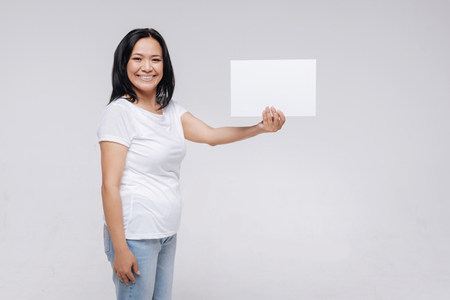 Cheerful elegant woman showing a white piece of paper