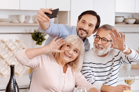 Smiling man taking selfie with senior parents at home Stock Photo