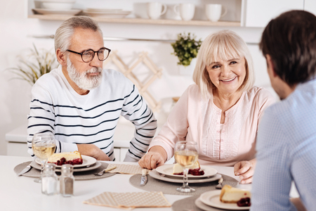 relishing: Peaceful elderly couple relishing dinner with their kid at home