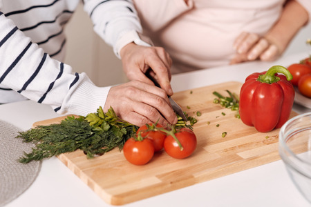 Preparing nutritious salad together. Peaceful harmonic aged couple standing in the kitchen and cooking healthy dinner while expressing care