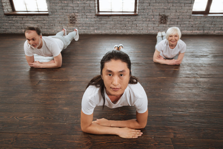 gerontology: Yoga instructor leaning his elbow on the floor