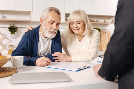 Delightful elderly couple signing documents at home