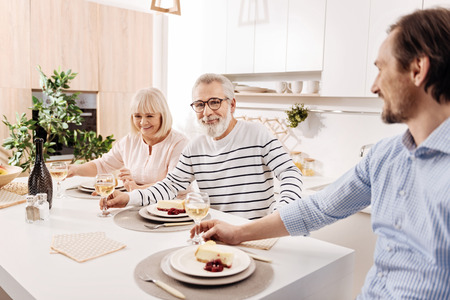 Positive elderly parents enjoying weekend with son at home
