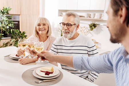 relishing: Smiling elderly couple relishing dinner with their child at home Stock Photo